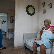 "Punto Santiago, PR--TeÛfila Delgado shows her ""determined look"" for her daughter, Carmen Camacho inside their home, November 8, 2017. Carmen, her mother, and five additional family members stayed in their home to ride out Hurricane Maria because her mother refused to leave. At about 6am on September 20, 2017, their home flooded quickly and they had to escape out of a bedroom window and move to the second floor of their home, which by that time had no roof. For the next six hours, they were exposed to a hurricane, whose eastern wall passed over their community. Photo by Lori Waselchuk/braf.org"