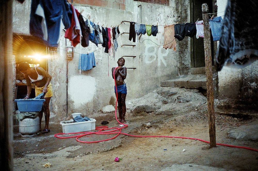 Due to the lack of infrastructure, water supply is often scarce and has to be stolen from government pipelines. Houses hardly ever enjoy running water and often have to share. Tasks such as laundry and showers are therefore often done in the street. Rio de Janerio, Brazil. 2001