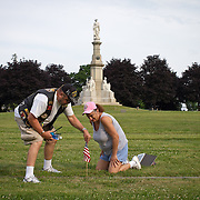 Jim Remmy and his wife, Sharon, plant a flag for Sharon's Great, Great, Uncle, Leander Burnham, buried at Soldiers National Cemetery, during the Sesquicentennial Anniversary of the Battle of Gettysburg, Pennsylvania on Sunday, June 30, 2013.  A pivotal moment in the Civil War, over 50,000 soldiers were killed, wounded or missing after 3 days of battle from July 1-3, 1863.  Later that year, President Abraham Lincoln returned to Gettysburg to deliver his now famous Gettysburg Address to dedicate the cemetery there for the Union soldiers who died in battle.  John Boal photography