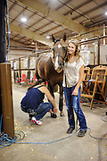 Youth from around the world converged on Oklahoma City for the American Quarter Horse Assocation (AQHA) Youth World horse show at the Oklahoma City Fairgrounds.  Each participant had to qualify either at the state or national level to compete.  All contestants under age 18 and horse must be owned by them or a direct family member...Paige Wacker from Hutchison Minnesota holds her horse while her mom Shannon prepares horse hooves for competition, competing in showmanship class..