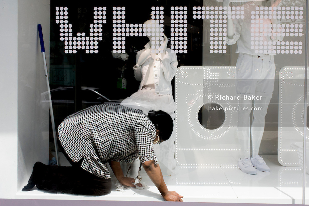 Window dresser cleans and tidies the floor in a central London retail display.