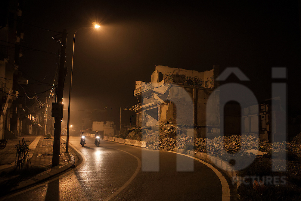 At night, two motorbikes ride in Hoang Hoa Than street. Beside the road, houses are demolished. Hoang Hoa Tham steet, hanoi, Vietnam, Asia.