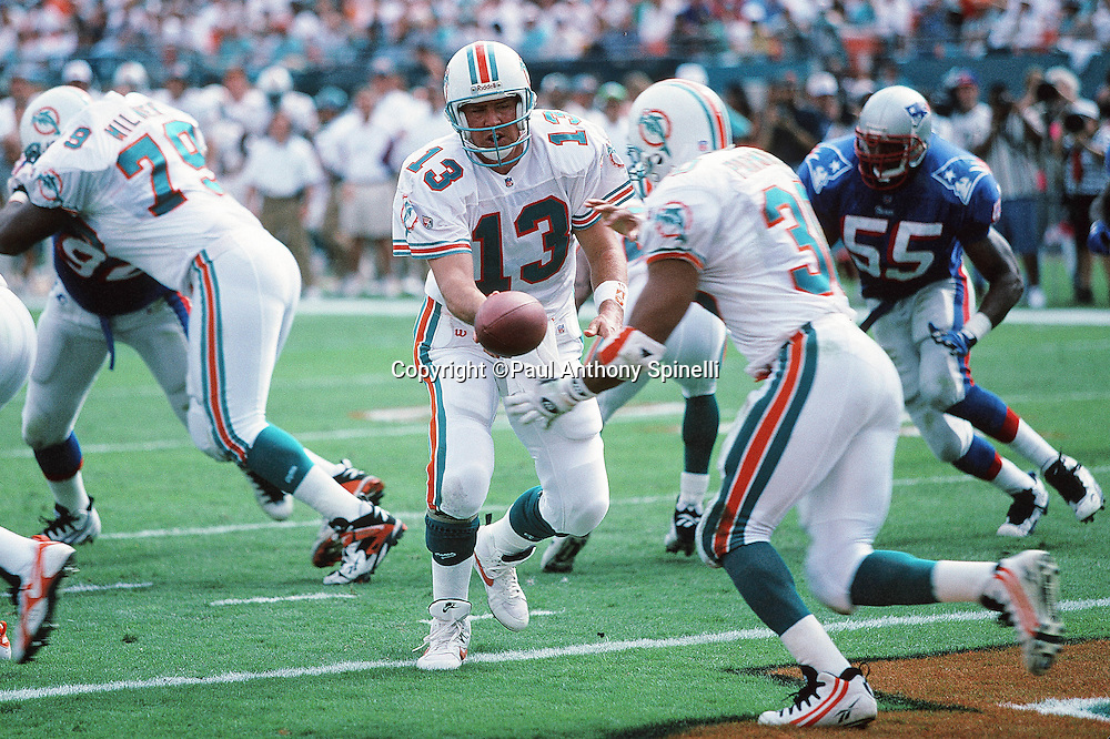 Miami Dolphins quarterback Dan Marino (13) hands off the ball on a running play to Dolphins running back Bernie Parmalee (30) during the NFL football game against the New England Patriots on Nov. 12, 1995 in Miami Gardens, Fla. The Patriots won the game 34-17. (©Paul Anthony Spinelli)