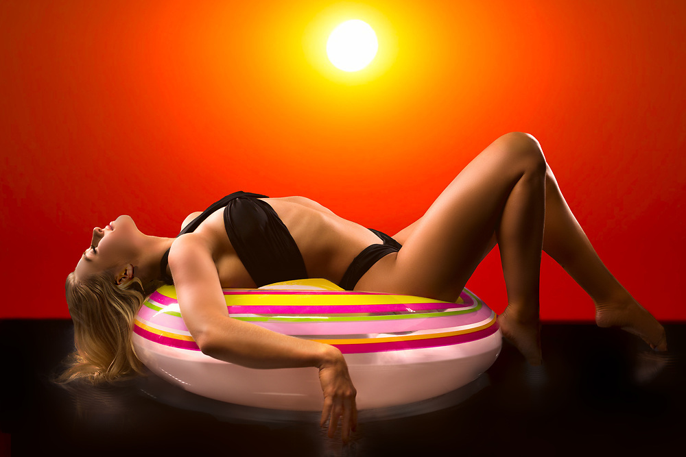Fashion photo of swimsuit model lying on colorful inner tube against orange sky. By Gerard Harrison, Image Theory Photoworks. Model Savannnah O'Hara.