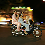 A decade ago Vietnams roads were teaming with bicycles. But as the countries economic growth increased bringing relative affluence to the working class, the push bike has been replaced by the scooter as the main mode of transport for the nations population.. Ho Chi Minh City alone has an estimated three million scooters buzzing around the streets day and night. Everyday life is dominated by the site of the scooter. Street corners have become parking lots for rows upon rows of parked scooters.. Puncture repair workmen wait on every city street to come to the aid of the rider with a blown tyre, and make a quick buck in the process, while families have a night on the town together, all seated on the same scooter!.Any number of items can be seen transported on the back of a scooter, from pigs to wardrobes anything that can be tied down is moved on the trusted scooter..Even in the outlying country areas the scooter is now used to transport produce to and from the markets. While even beach goers at the coastal towns head for a swim and a sunbathe accompanied by their scooter. .A night on the town for a family in Ho Chi Minh City on September 29, 2006. Photo Tim Clayton