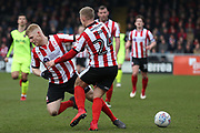 Lincoln City midfielder Danny Rowe (24) and his team mate clash during the EFL Sky Bet League 2 match between Lincoln City and Exeter City at Sincil Bank, Lincoln, United Kingdom on 30 March 2018. Picture by Mick Atkins.