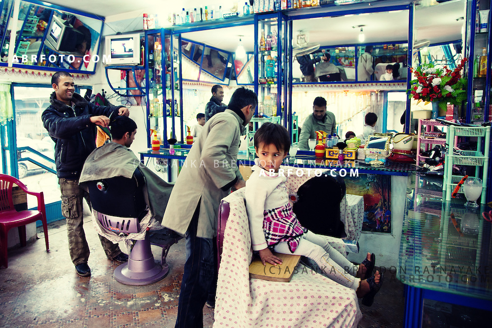 A young Afghan girl gets her haircut at a barber shop in Kabul.