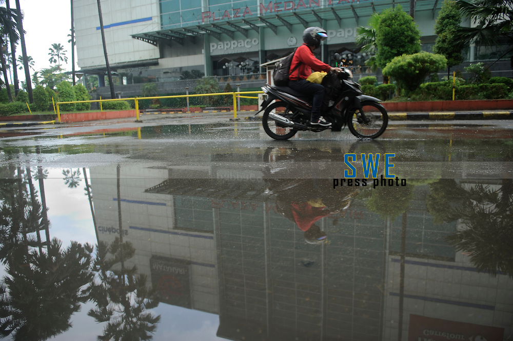 Medan, Indonesia, March 28, 2020: A motorist seen riding at the front of the main store of Medan beside the daily socialization and disinfection of the Corona Virus Disease 19 spread dangers in North Sumatra province, Indonesia on March 28, 2020.