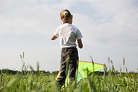 Young girl flying kite in field