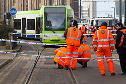 © Licensed to London News Pictures. 17/02/2012, London, UK.  Rail workers check the track in front of a derailed tram at East Croydon tram stop in Croydon, South London, Friday, Feb. 17, 2012. Photo credit : Sang Tan/LNP