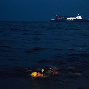 Triathlete Paul Parrish is passed by a passenger ferry as he undertakes the swim section of his Arch to Arch triathlon attempt in the busiest shipping lane in the Channel between England and France September 15, 2014.