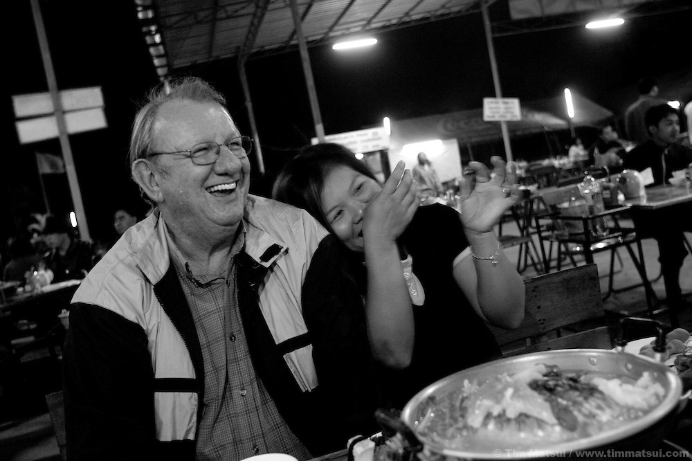 Ted, a 62 year-ol Canadian expatriate and his mid-thirties Thai wife Lam out to dinner in Chiang Mai, Thailand. Ted's introduction to Thailand was through sex tourism; his friend Eric simply came to escape depression and post traumatic stress from multiple accidents as a commercial truck driver. Both can live in greater comfort in the relatively inexpensive Thailand, not work, support their partner's, and do things like build houses for themselves and their partners' families. Like many older expats, they have left behind caucasian wives and children and found younger Thai women. While Eric's sentiments towards his partner may be different, Ted, who is 62 years old, expressed that he does not have a idyllic, youthful love for his wife but that they care and have an understanding for each other. Plus, he says, the men can live like millionaires and for the women it's like they've won the lottery.