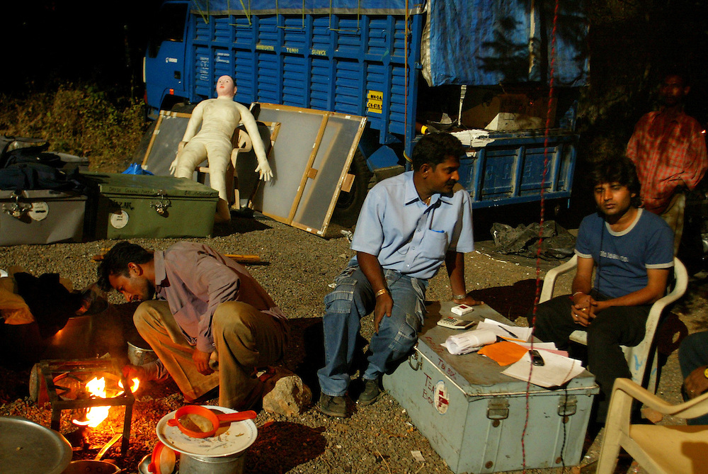 Prop assitants make tea as they try to keep awake and alert in the wee hours of the morning on the set  of an action movie in film city in the outskirts of Bombay, India Dec. 8, 2004.Bombay's film industry may be the most prolific in the.world, but unlike it's American counterpart, much of.the work is done on a shoestring. The city churns out.hundreds of films a year on its celluloid production.line. And while Hollywood has millions to spend on.marketing and advertising, in Bollywood, many of the.billboards for the biggest releases are painted by.hand. It's a dying art, but one that has a romance all.of its own. .
