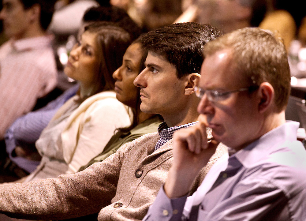 Four businesspeople sitting in audience listening during business meeting.