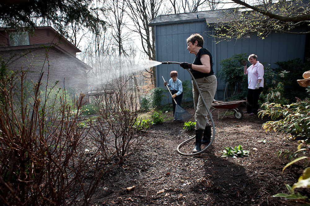 COLUMBIA, MD -- 3/23/12 - Mary Ament Streb (center), puts some water on her plants as Georgia Eacker, left, and Linda Decker-Hartman tend to some loose ends....The Howard County Master Gardeners is part of the University of Maryland Extension program, and this club's focus has evolved into stewardship and conservation. Georgia Eacker is the club's Master Gardener Coordinator, Mary Ament Streb is a master gardener and member of Baywise, and Linda Decker-Hartman is the Baywise Coordinator. The three gathered at the home of Mary Ament Streb, who has replaced all the grass in her yard with various types of ground cover.by André Chung #AC2_6130