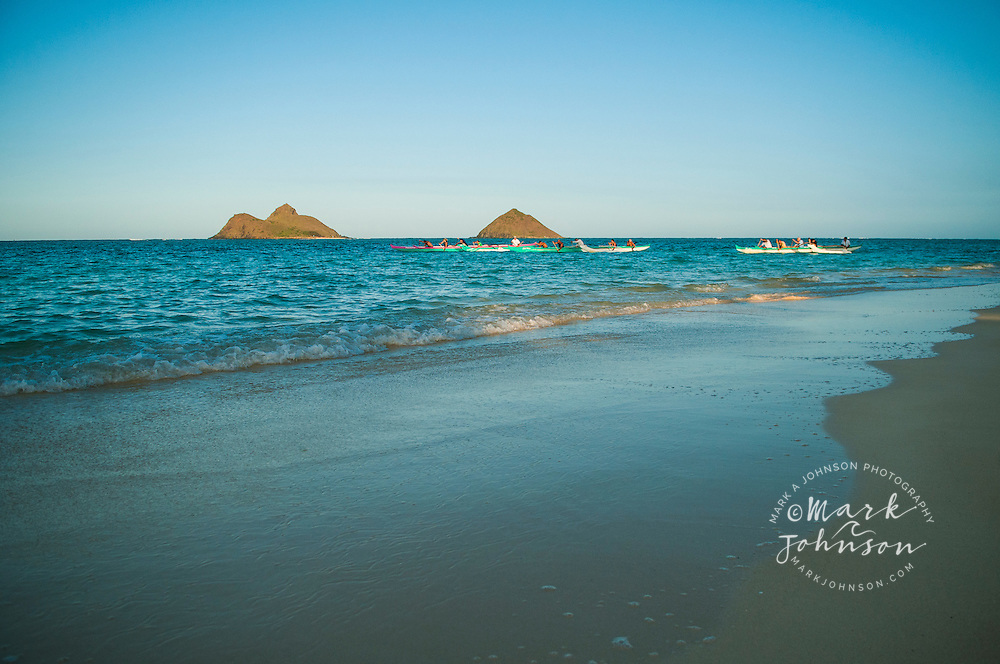 Outrigger canoes off Lanikai Beach, Mokulua Islands offshore, Kailua Bay, Oahu, Hawaii
