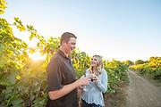 Couple enjoying wine while walking through the vineyard at Holeinsky Winery in Buhl, Idaho.