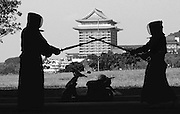 GRAND BATTLE<br /> Kendo practitoners spar underneath a bridge in a river valley park. Many parts of Japanese culture are evident in Taiwanese society no doubt the result of several years of colonization.The landmark Grand Hotel is in the background.