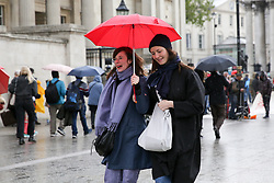 © Licensed to London News Pictures. 04/05/2019. London, UK. Women shelter under an umbrella in Trafalgar Square as it starts rain. Photo credit: Dinendra Haria/LNP