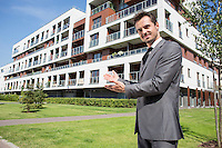 Portrait of confident real estate agent showing office building