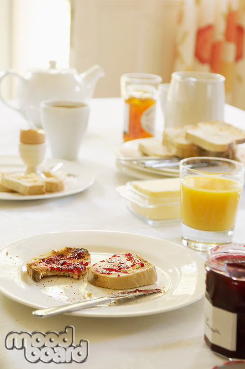 Plate with half-eaten toast covered in jam on table set for breakfast