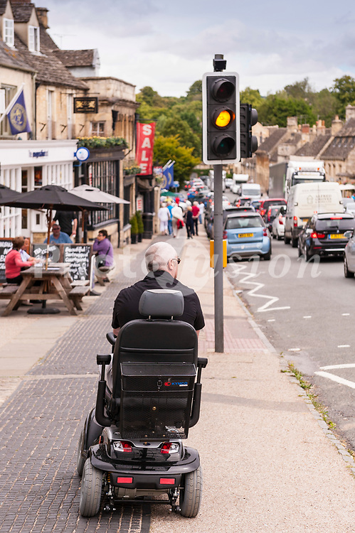 A man on a dissability scooter in the pretty Cotswold town of  Burford , Oxfordshire , England , Britain , Uk