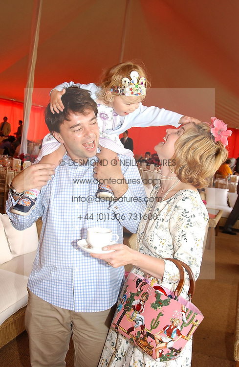 Cabaret star BARONESS ISSY VAN RANDWYCK and her husband MR EDWARD HALL son of Peter Hall with their daughter GEORGIA at the Veuve Clicquot sponsored Gold Cup or the British Open Polo Championship won by The  Azzura polo team who beat The Dubai polo team 17-9 at Cowdray Park, West Sussex on 18th July 2004.