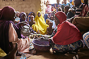 Fati Kabidou, mother of eight children demonstrates hand washing to a group of villagers during a hygiene awareness program in the village of Loga, Tera region, Niger on May 20, 2015. Fati and her husband Issa have a recently installed latrine nearby their home. Before the women, seeking privacy would walk into fields or down by the river to relieve themselves. UNICEF working in partnership with NGO SNV promotes a water, sanitation and hygiene program piloted by members of the community. The program includes awareness on hand washing and construction of latrines within the village.