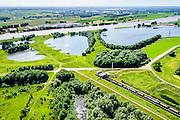 Nederland, Gelderland, Duiven, 09-06-2016; Groessen, natuurgebied Kandia. Goederentrein op Betuweroute, tunnel onder Pannerdensch kanaal met dienstgebouw.<br /> Tunnel Betuweroute, freight railway, Pannerdensch channel (Lower Rhine) on the horizon.<br /> <br /> luchtfoto (toeslag op standard tarieven);<br /> aerial photo (additional fee required);<br /> copyright foto/photo Siebe Swart