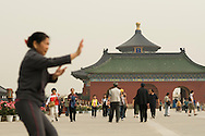 A woman practicing tai chi in front of the Temple of heaven.