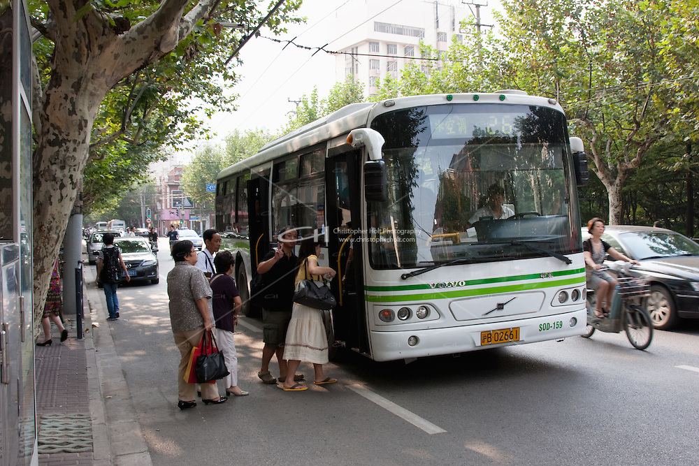 bus in shanghai with people boarding, china.