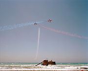 Hawk jets of the Red Arrows, Britain's RAF aerobatic team practice their display using an old ship wreck as display datum (centre). The wreck is the MV Achaios. Built in 1932, it was on a voyage from Yugoslavia to Jeddah in 1976 with a cargo of timber. She ran aground in a storm at Akrotiri Peninsula, but no lives were lost.