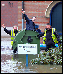 workers on a commercial site  in Egham use a bin to move around as floods hit the town, United Kingdom, Wednesday, 12th February 2014. Picture by Andrew Parsons / i-Images