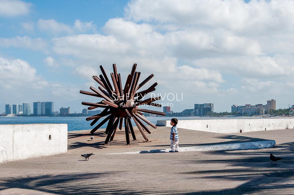 On the Puerto Vallarta malecon a small child contemplates Eriza-Dos, the iron sea urchin modern sculpture by artist Blu.