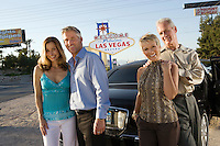 Two women and two men posing in front of Welcome to Las Vegas sign, group portrait