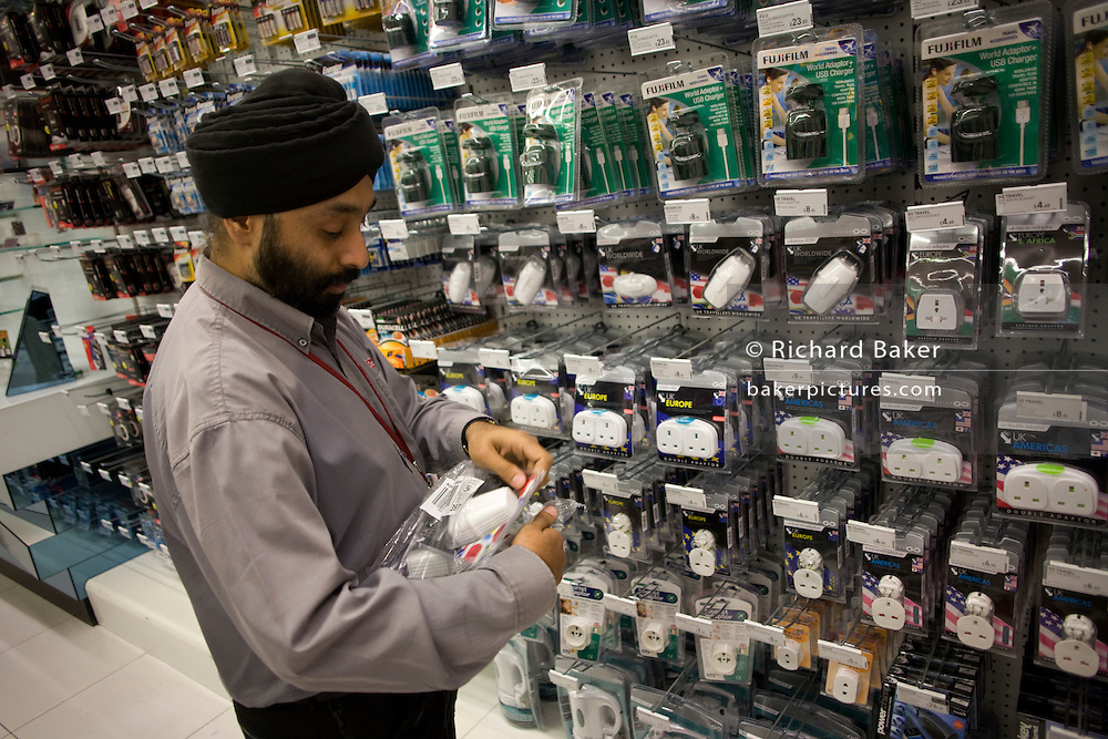 A sales assistant with Dixons Digital replenishes shelves with travel adapters and plugs at Heathrow airport's terminal 5
