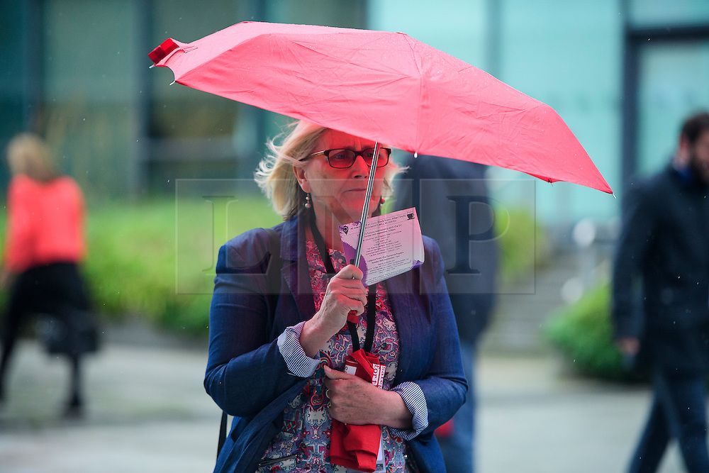 © Licensed to London News Pictures. 26/09/2016. Liverpool, UK. Labour delegates sheltering from the rain underneath umbrellas as they arrive for day two of the Labour Party Annual Conference, held at the ACC in Liverpool, merseyside, UK. Photo credit: Ben Cawthra/LNP
