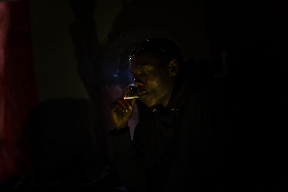 Calais, Frankreich - 16.10.2016<br /> Ein Migrant aus dem Sudan raucht im Dschungel von Calais in einer H&uuml;tte eine Zigarette. Das Fluechtlingscamp an der Kueste zum Aermelkanal soll laut franz&ouml;sischer Regierung in den n&auml;chsten Tagen geraeumt werden. In dem Camp leben um die 1000 Fluechtlinge und warten auf die Moeglichkeit zur Weiterreise durch den Eurotunnel nach Gro&szlig;britannien. Photo: Foto: Markus Heine / heineimaging<br /> <br /> Calais, France - 2016/10/16<br /> A migrant from Sudan smokes a cigarette in the Calais Jungle in a hut. The refugee camp on the coast to the English Channel is to be cleared in the next few days, according to the French government. In the camp live around the 1000 refugees and wait for the possibility to travel further through the Eurotunnel to the UK. Photo: Foto: Markus Heine / heineimaging<br /> <br /> ------------------------------<br /> <br /> Ver&ouml;ffentlichung nur mit Fotografennennung, sowie gegen Honorar und Belegexemplar.<br /> <br /> Bankverbindung:<br /> IBAN: DE65660908000004437497<br /> BIC CODE: GENODE61BBB<br /> Badische Beamten Bank Karlsruhe<br /> <br /> USt-IdNr: DE291853306<br /> <br /> Please note:<br /> All rights reserved! Don't publish without copyright!<br /> <br /> Stand: 10.2016<br /> <br /> ------------------------------