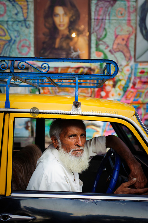 A taxi cab in front of a brightly decorated building, Mumbai, India.  In 2006 the city of Mumbai mandated that all public transportation be run on Compressed Natural Gas or CNG.  This green shift has vastly improved air quality in the city of Mumbai.