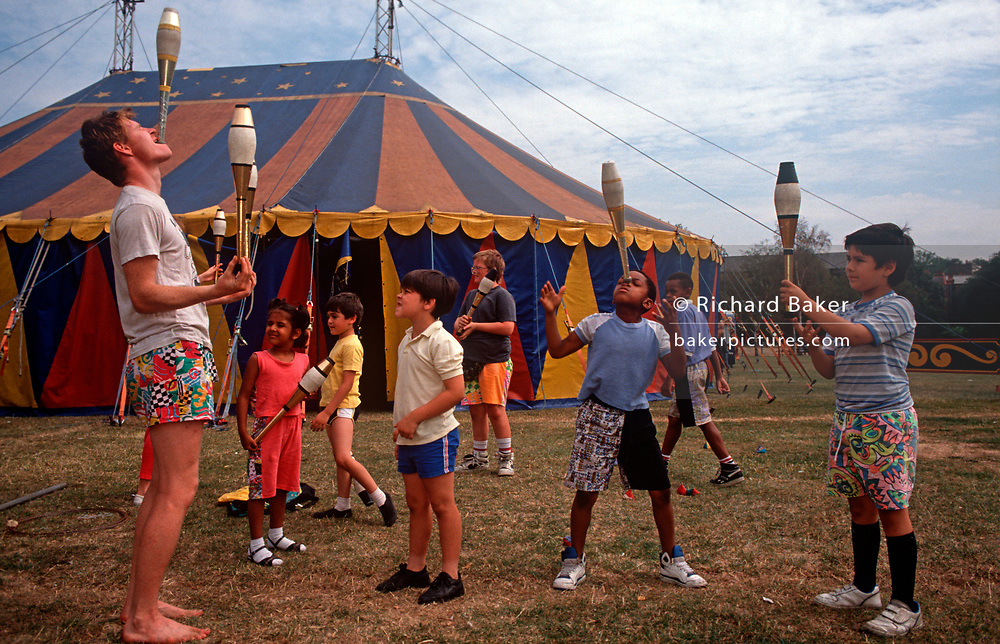 Schoolchildren of various ages learn circus skills from a circus performer with the small Snapdragon Circus, on 28th September 1990, in London, England. (Photo by Richard Baker / In Pictures via Getty Images)