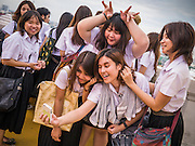 "27 NOVEMBER 2012 - BANGKOK, THAILAND:  School girls pose for photos with their smart phones at Wat Saket during the temple's annual fair. Wat Saket, popularly known as the Golden Mount or ""Phu Khao Thong,"" is one of the most popular and oldest Buddhist temples in Bangkok. It dates to the Ayutthaya period (roughly 1350-1767 AD) and was renovated extensively when the Siamese fled Ayutthaya and established their new capitol in Bangkok. The temple holds an annual fair in November, the week of the full moon. It's one of the most popular temple fairs in Bangkok. The fair draws people from across Bangkok and spills out in the streets around the temple.   PHOTO BY JACK KURTZ"