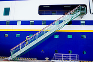 A passenger climbs the gangway of a cruise ship in a traditional vietnamese hat, Ho Chi Minh city, Vietnam.