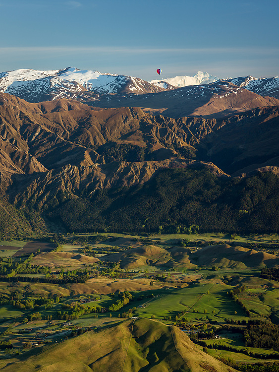 A hot air balloon flies near Coronet Peak. Morven Hill is in the foreground and Aoraki Mount Cook in the distance. Otago, New Zealand.
