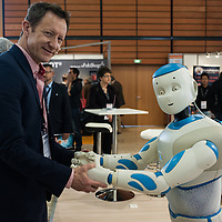 Lyon, France - 19 March 2014: An exhibitor holds the hands of NAO Robot by Aldebaran at Innorobo 2014, the biggest fair in Europe for robotics.