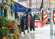 © Licensed to London News Pictures. 06/10/2014. Twickenham, UK. Water was forced into local businesses. Firefighters help to contain a mains water pipe which has burst in King Street Twickenham today 6th October 2014. It appears that workmen working in the area have used a JCB digger to stem the flow. Many local shops and businesses have been flooded.   Photo credit : Stephen Simpson/LNP