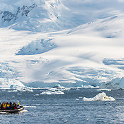 An inflatable dinghy with tourists explores Neko Harbour on the Antarctic Peninsula on a sunny day.