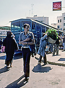 AFRICA; MOROCCO; TANGIER:  Street scene at bus station in Tangier with woman in burqah and man carrying mint leaves for tea.