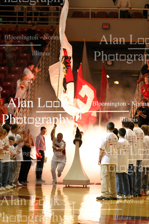 Cheerleaders appear through lighted smoke to lead the way for the Illinois State Redbird Men's basketball team.