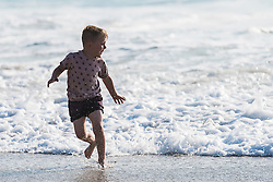 A young boy plays in nthe sea on Fistral Beach in Newquay, Cornwall.