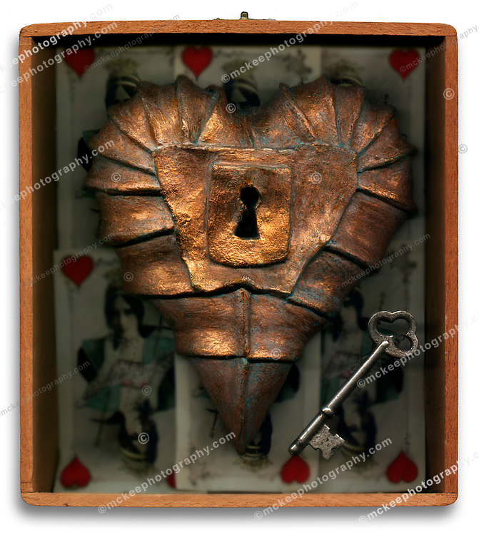 Armored brass Heart in a wooden box with a skeleton key. Love locked up.